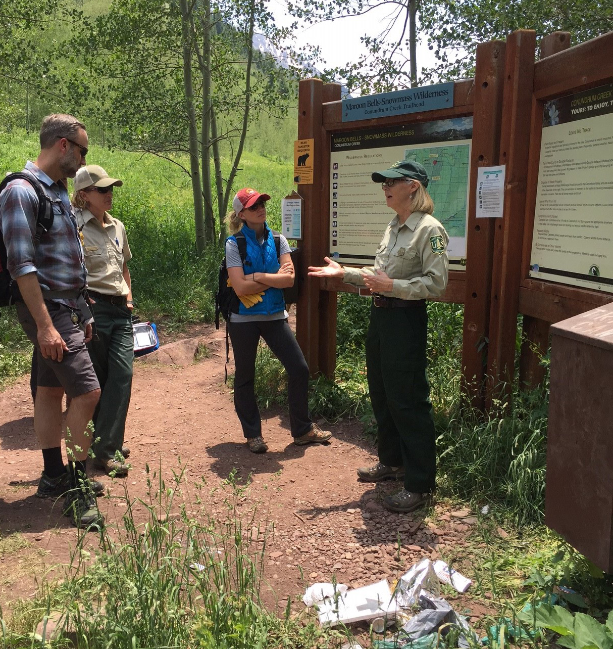 Photo: Woman in Forest Service uniform talks to hikers in front of a trail head sign littered with trash