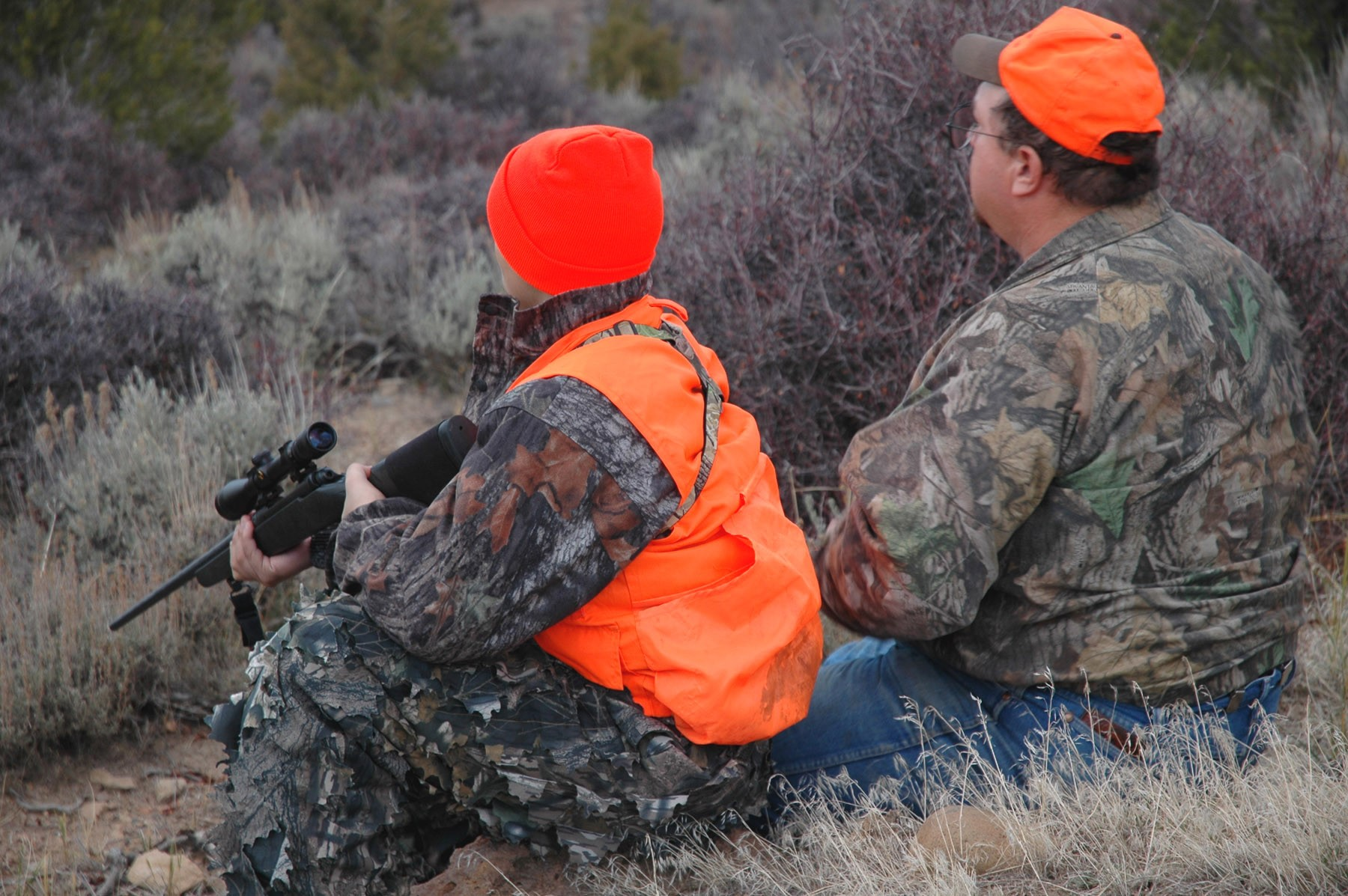 Two hunters sitting on the side of a hill wearing camouflage and hunter orange.