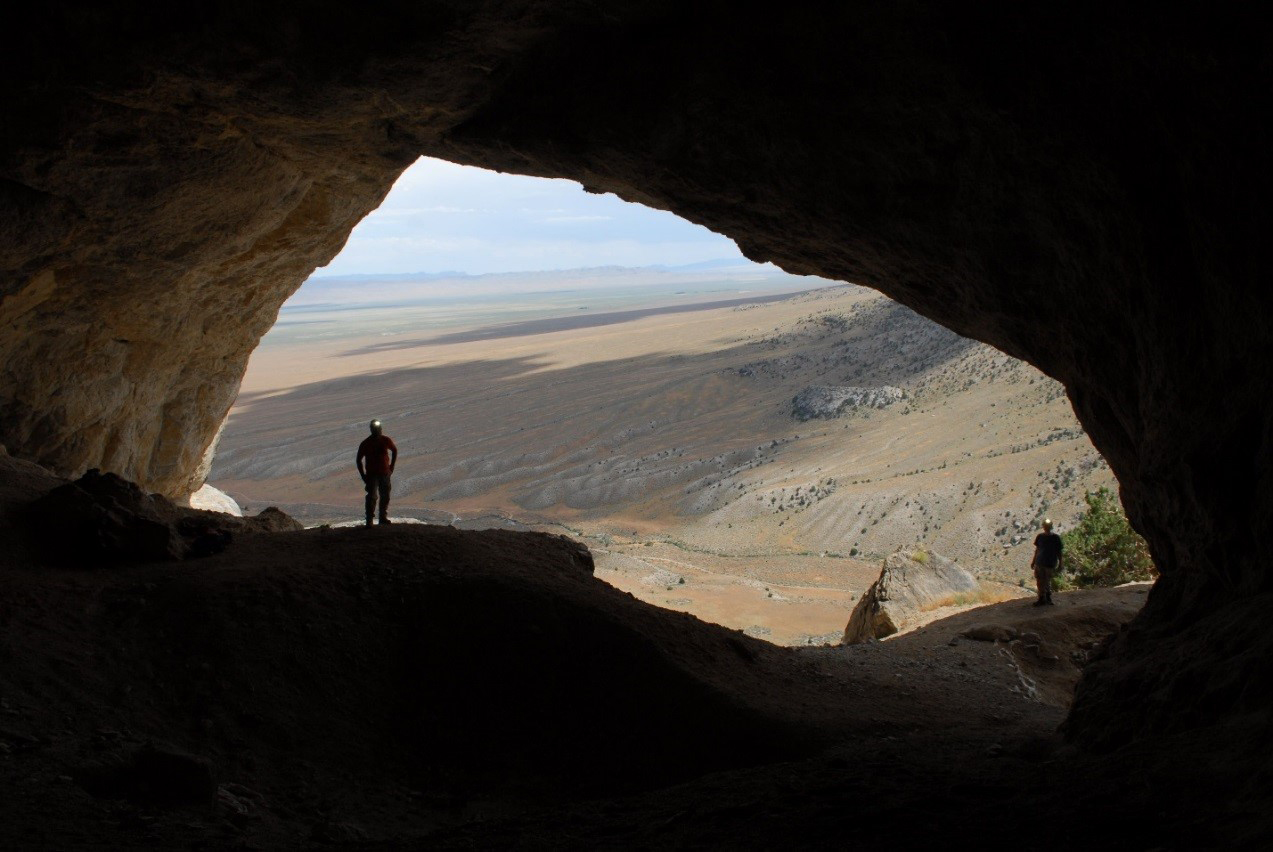 Photo: Two members of an inventory crew wearing helmets with spotlights enter a cave. Photo taken from within cave toward opening. Behind the people are hills of forest land.