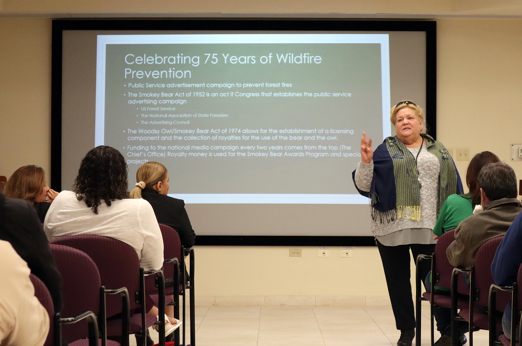 Iris Velez stands in the front of a conference room; behind her is a slide detailing a timeline of 75 years of wildfire history.