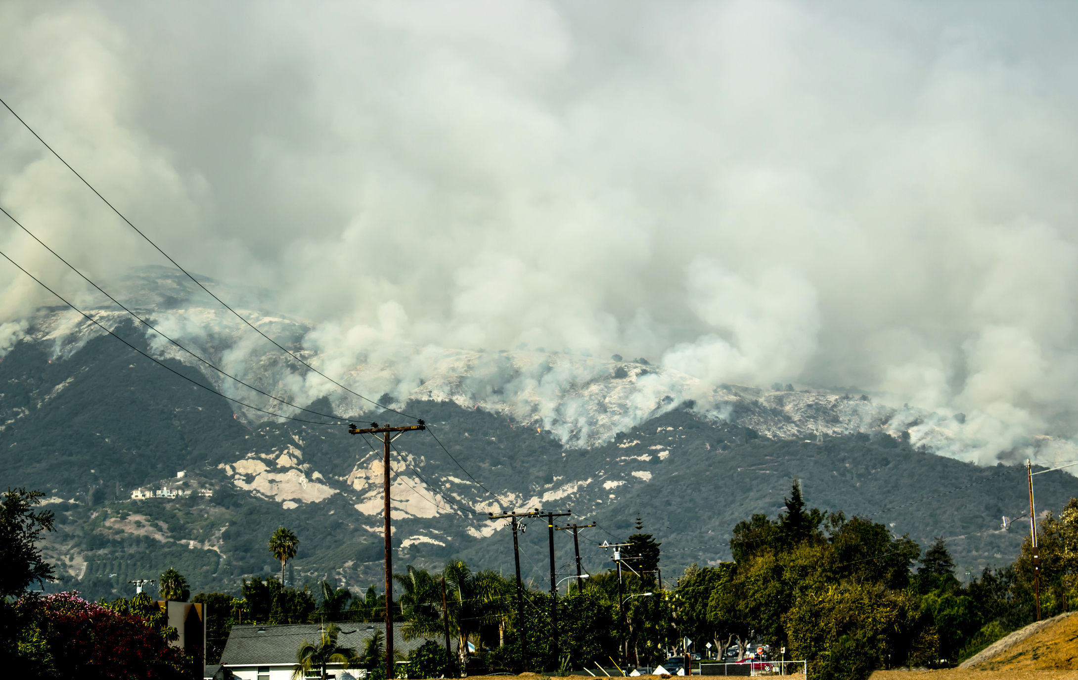 A picture showing a burning mountain side with smoke billowing into the air.