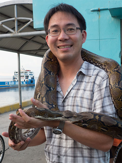 A photo of Joey Chong holding a boa constrictor