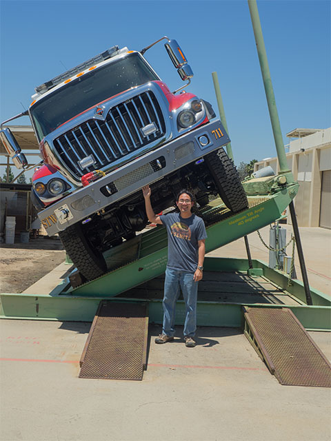 A photo of Joey Chong standing next to a truck testing fire apparatus during a tilt test to simulate driving conditions