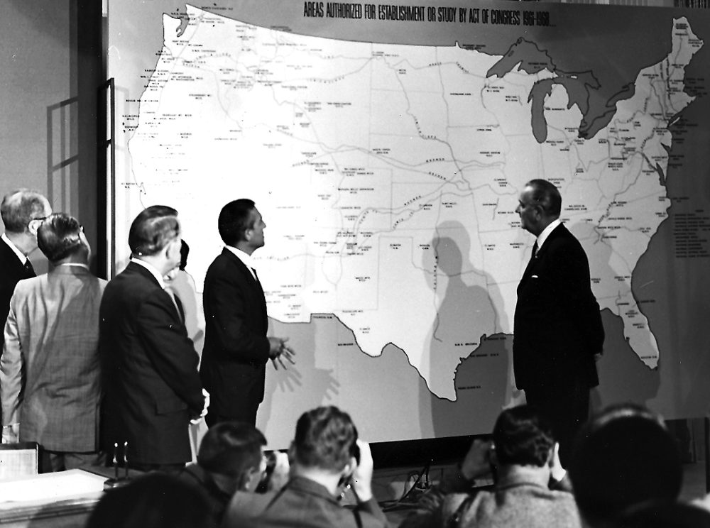 A black and white picture of President Johnson discussing a map of the proposed National Trails System
