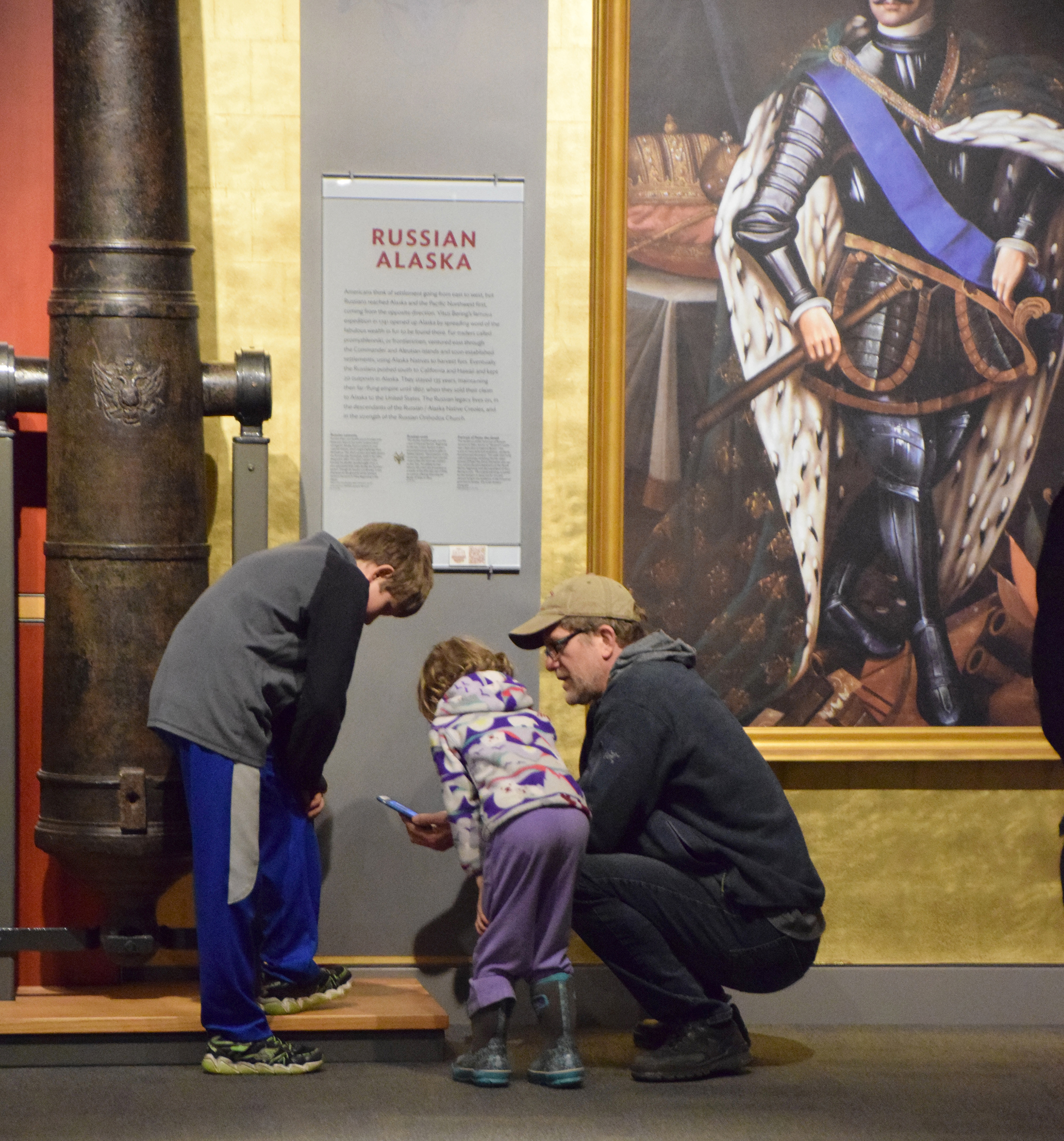Photo: Kids and their father peer at a smartphone as they investigate the museum.