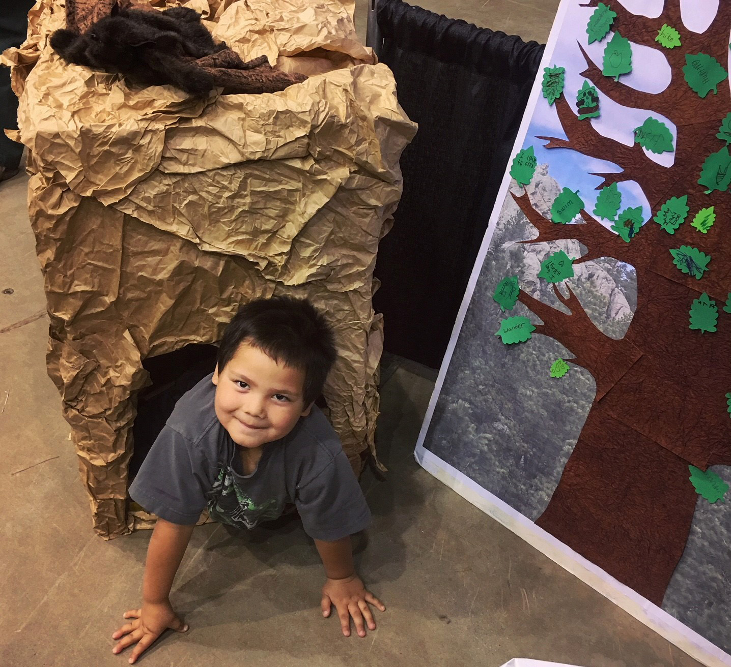Photo: A child looks up from the floor as he craws out of a paper cave.