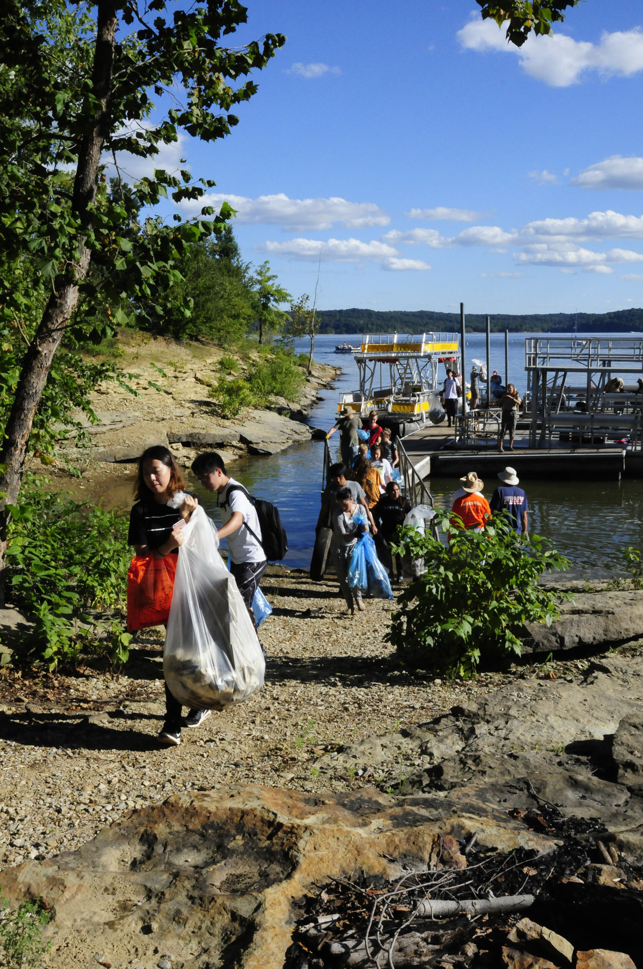 A photo of Volunteers disembarking from boat to remove trash