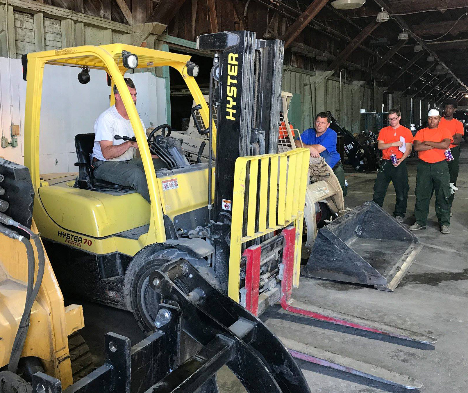 Photo: One student sits in a forklift while other students, trainer, look on.