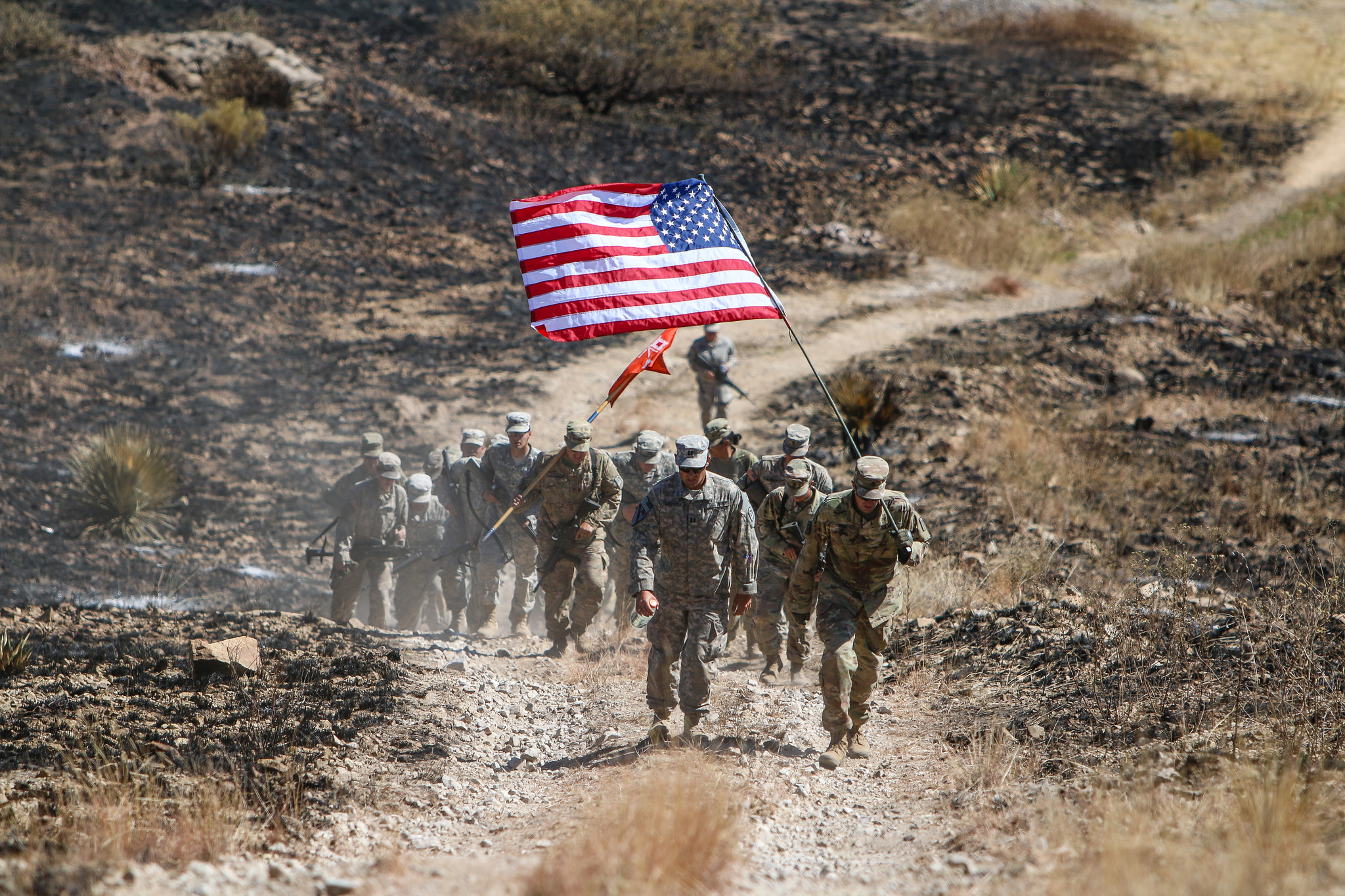 A picture of a group of soldiers hiking up a dusty road carrying two flags, a U.S. Flag and a flag for their unit.