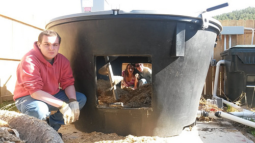 A photo of Boxelder math students Jacob Zulauf, Shaylee Habtemariam, and Conner Mylander work in the Earth Tub compost system
