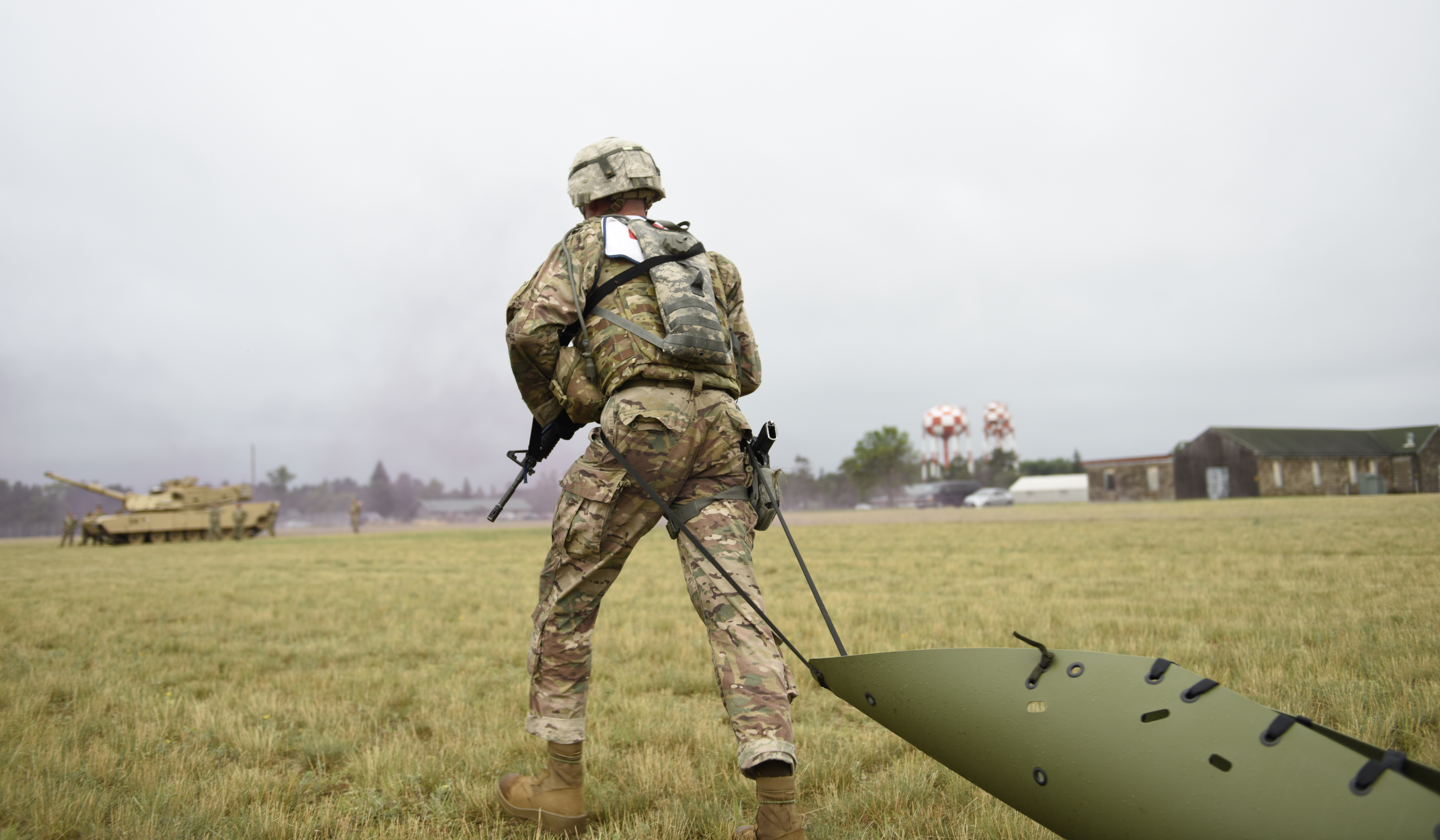 A picture of a military service member training by pulling a large object.