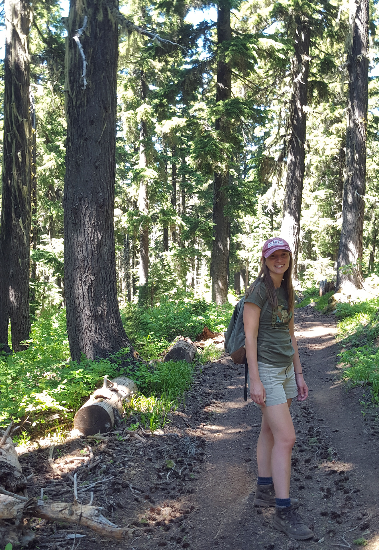 Photo: Woman poses on forest trail.