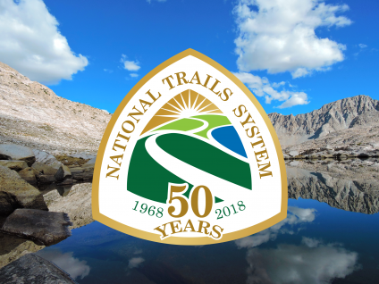 A picture with the National Trails System 50 years (1968 to 2018) logo and with high elevation lake and mountains in the background.