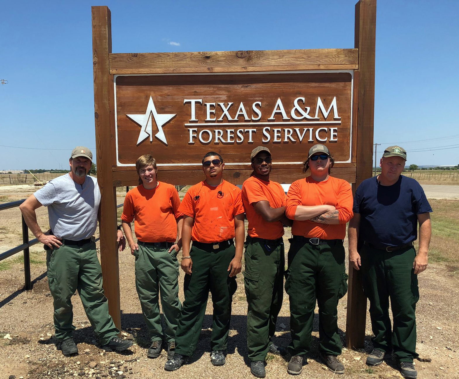 Photo: Group poses by Texas A&M Forest Service sign.
