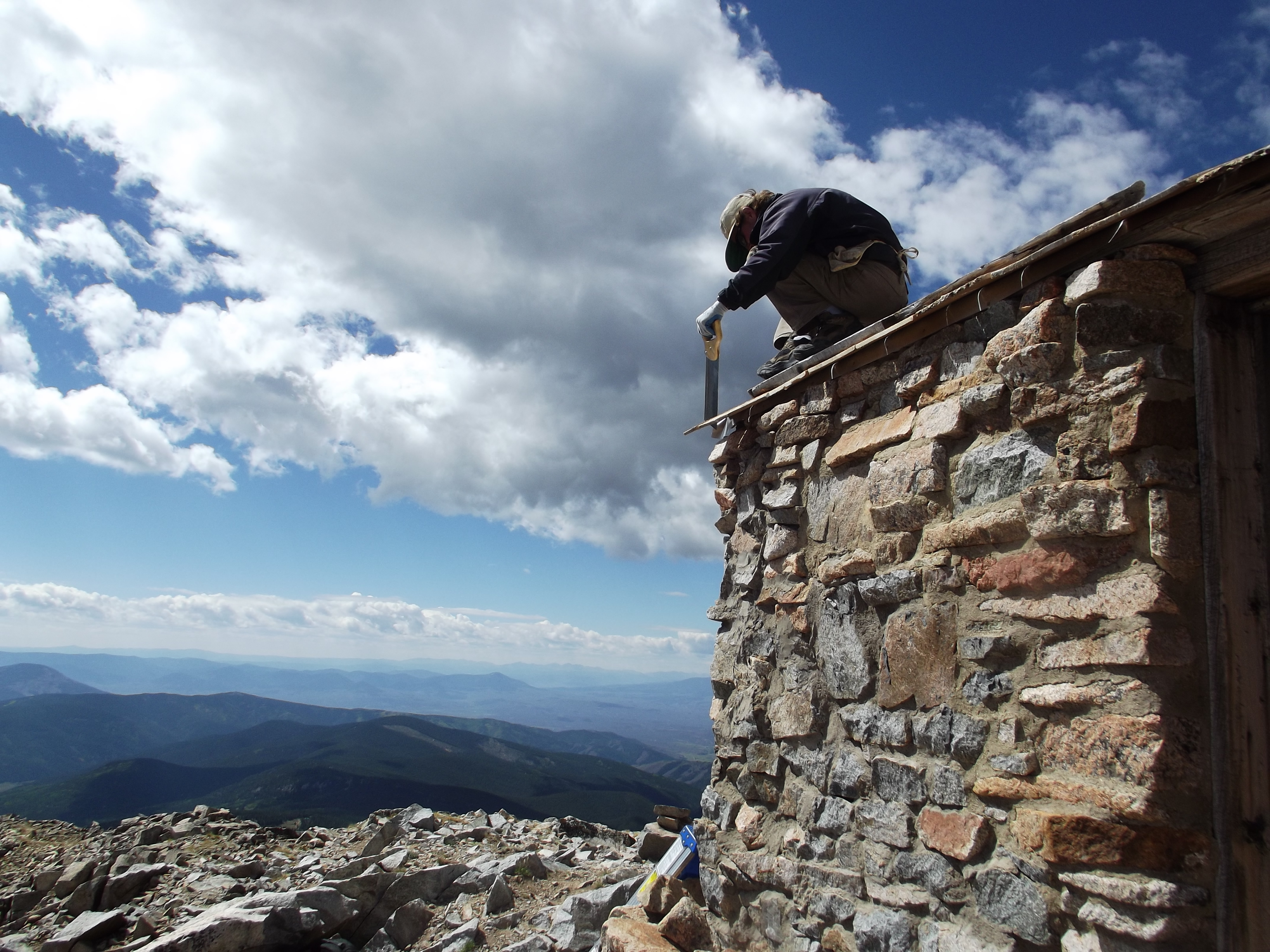 A HistoriCorps volunteer has a spectacular view while working on the Fairview Peak Fire Lookout on the Gunnison National Forest in Utah. The one-room lookout, the highest in North America, was built in 1912. (Photo courtesy Xavier Fane)