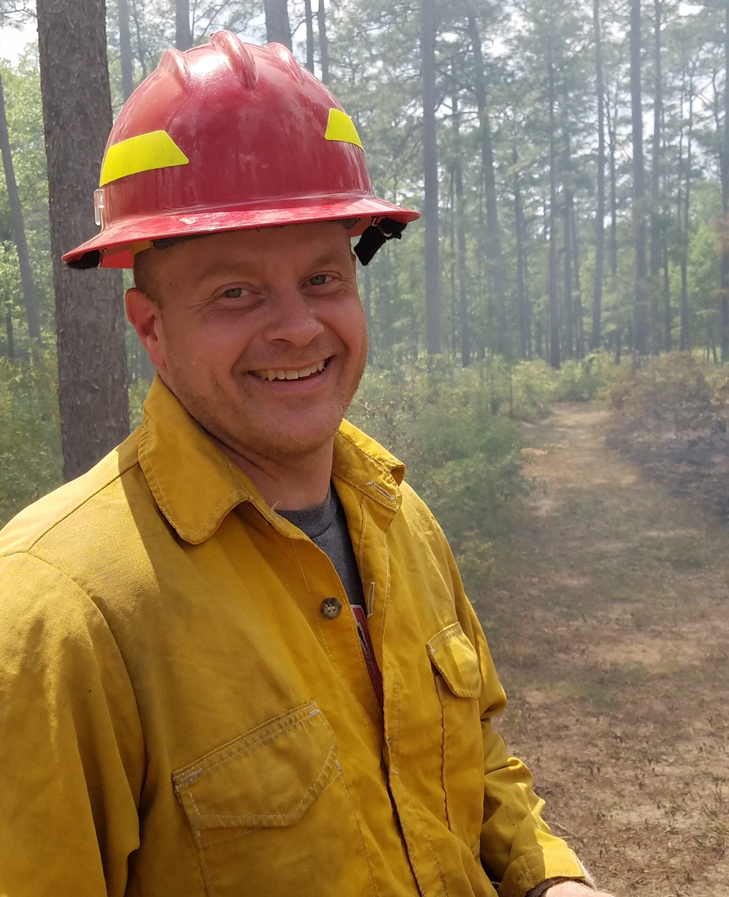A photo of Nick Skowronski wearing a red firefighter helmet and yellow fire shirt.