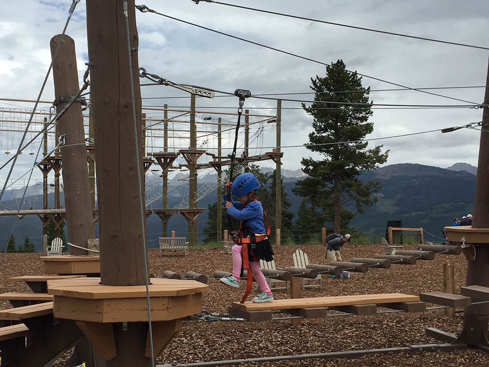 A photo of a young child participates in the Pine Cone Adventure Course at Vail Ski Area