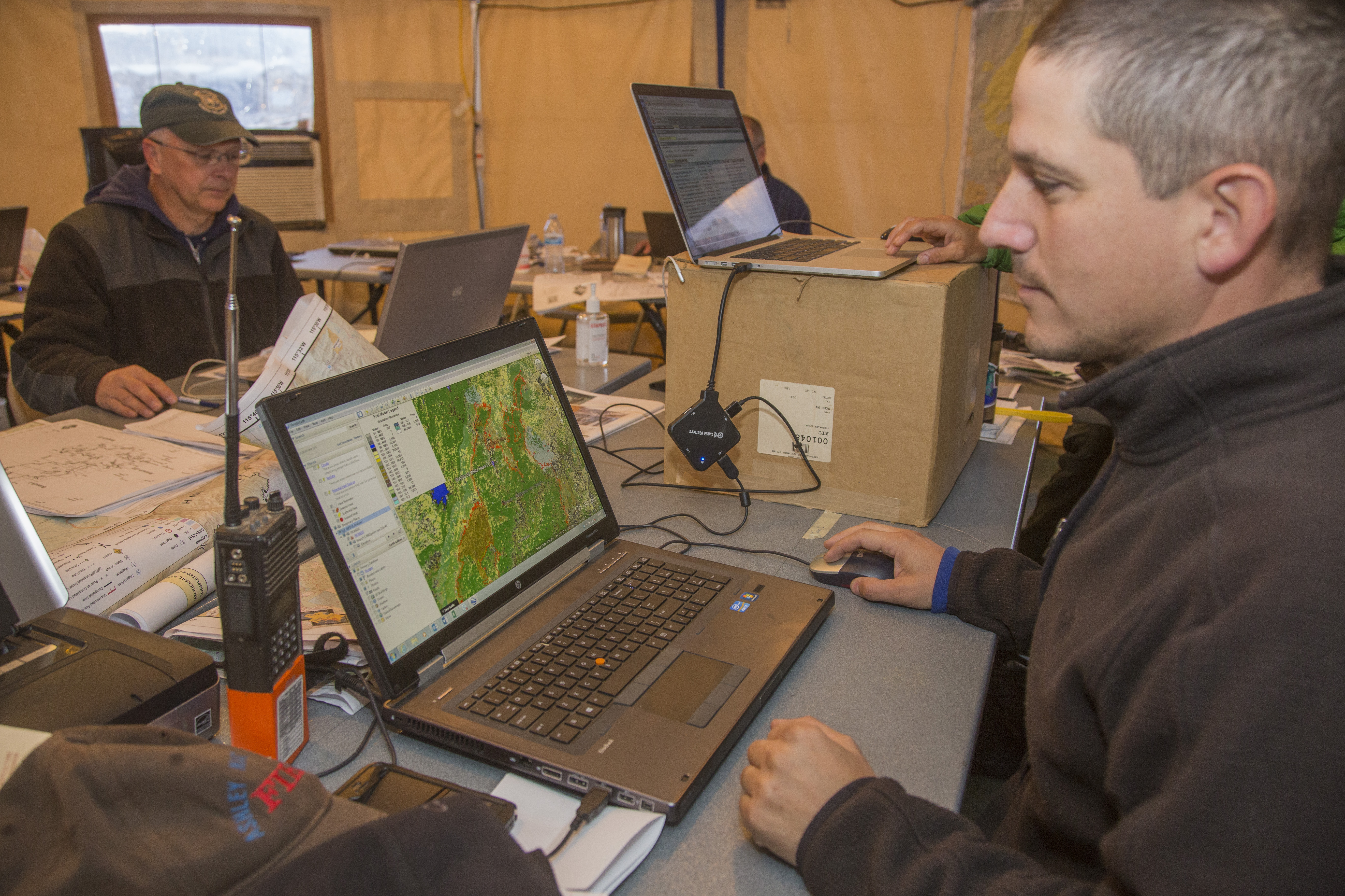 A picture of several members of a fire incident management team working on laptops.