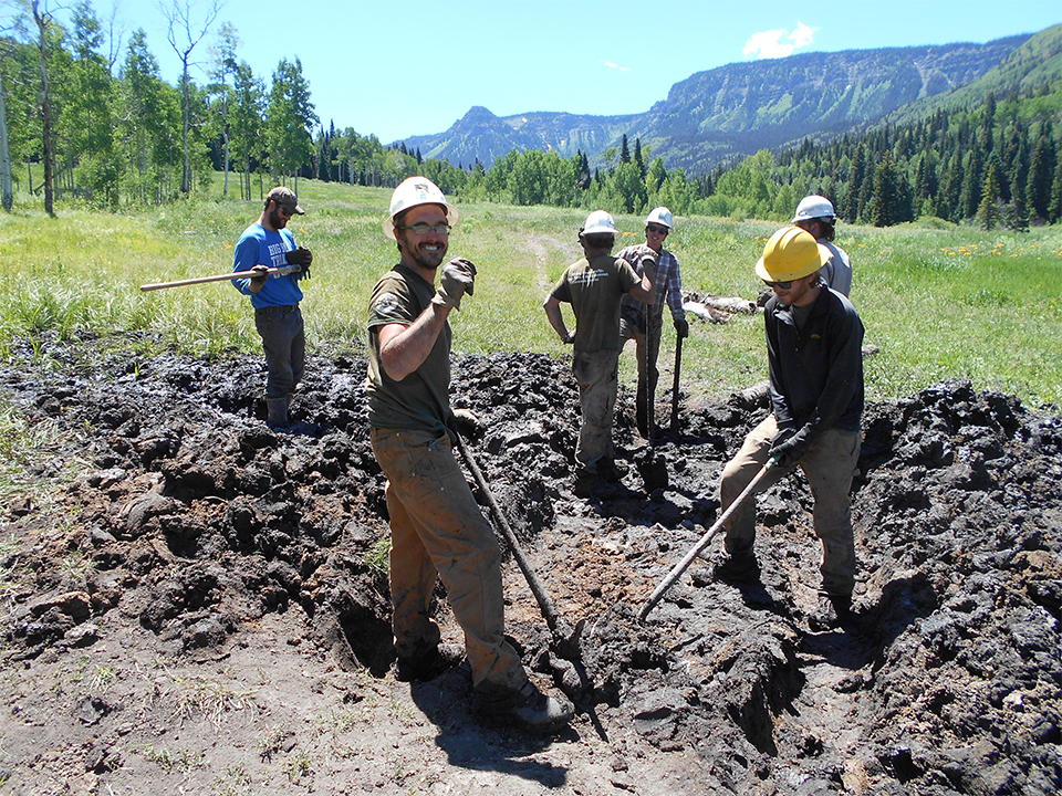 6 young men smile for the camera as they dig in a sunny field. In the background, there are beautiful mountains.