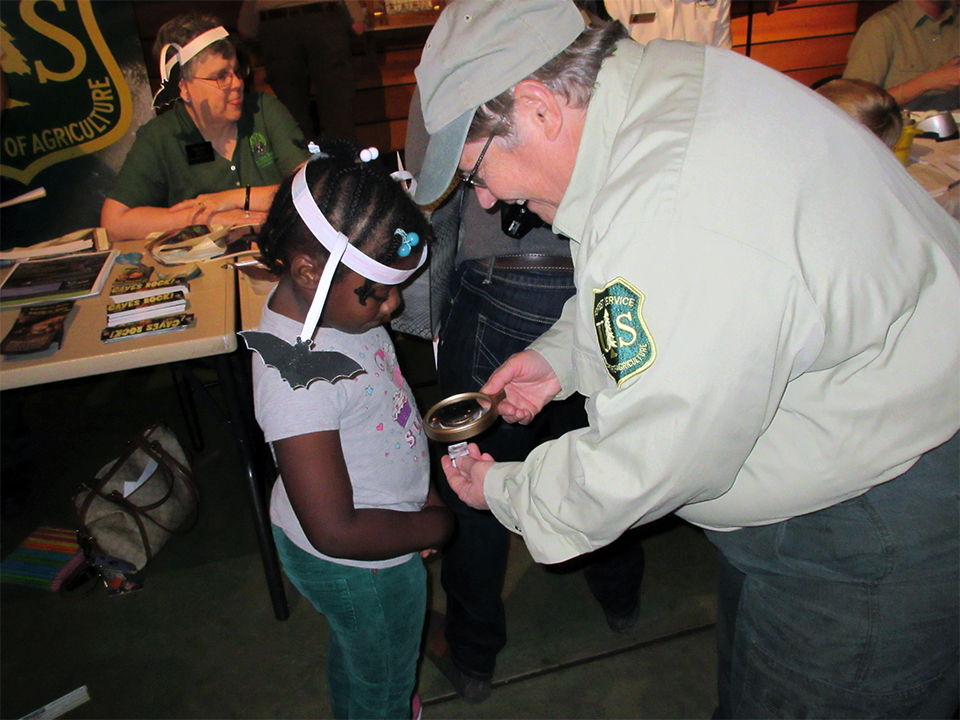 A photo of close up of a Forest Service employee showing a tiny bat skull and a magnifying glass to a young girl. The girl is wearing a paper crown with a paper bat hanging off of it.
