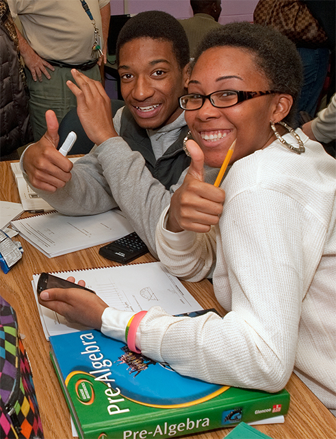 A photo of two smiling teenaged students sit at a desk with notebooks and a Calculus textbook. One of the teens is giving the 'thumbs up' with her hand.