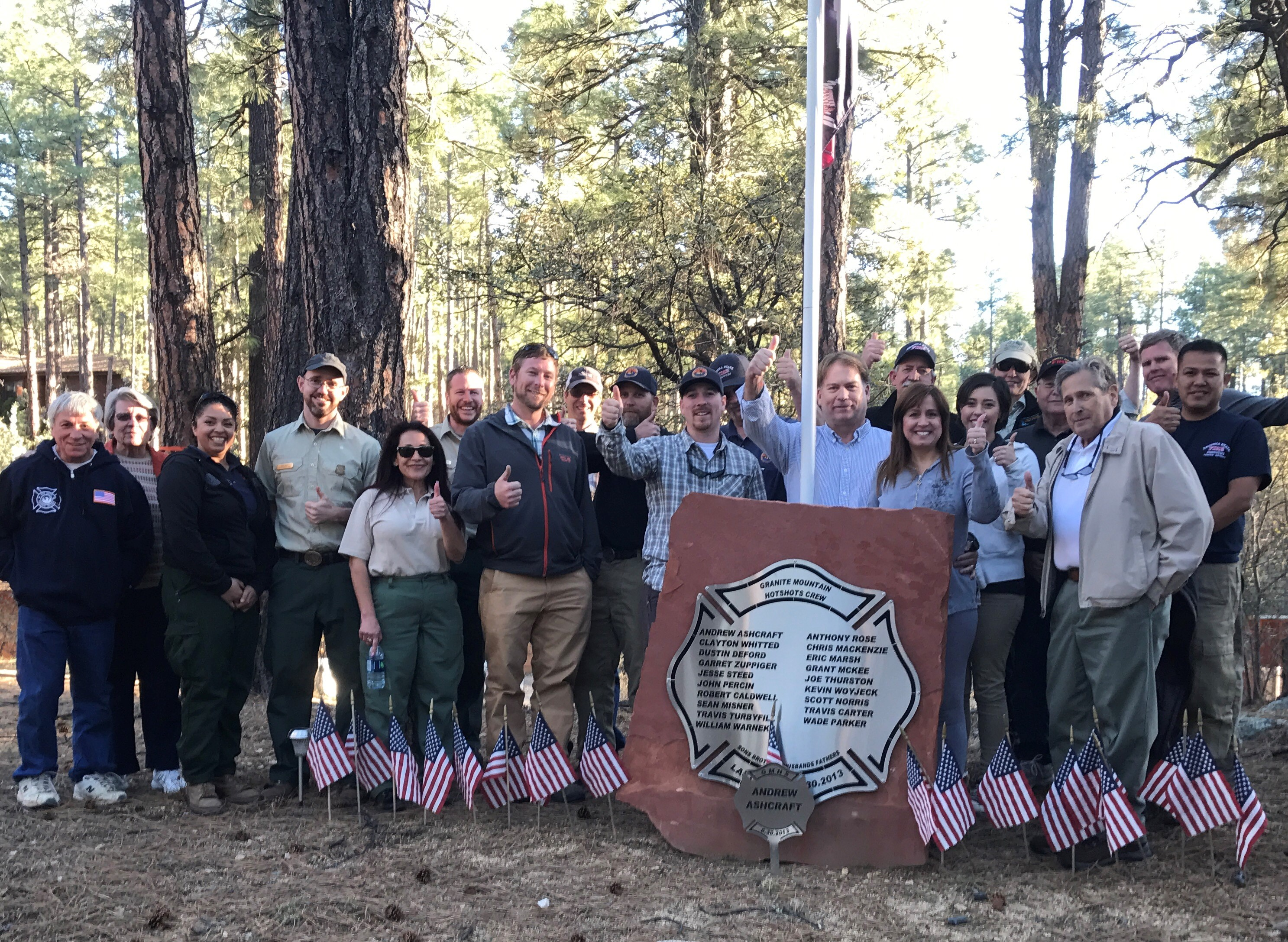 A large group of people gathered around a memorial, located on private land, dedicated to the Granite Mountain Hotshots who perished.