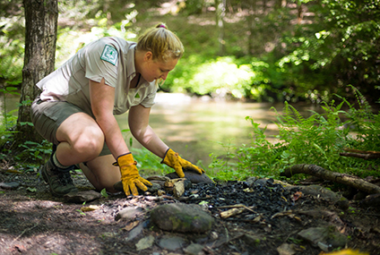A young woman wearing a Forest Service uniform constructs a fire ring at a backcountry campsite.