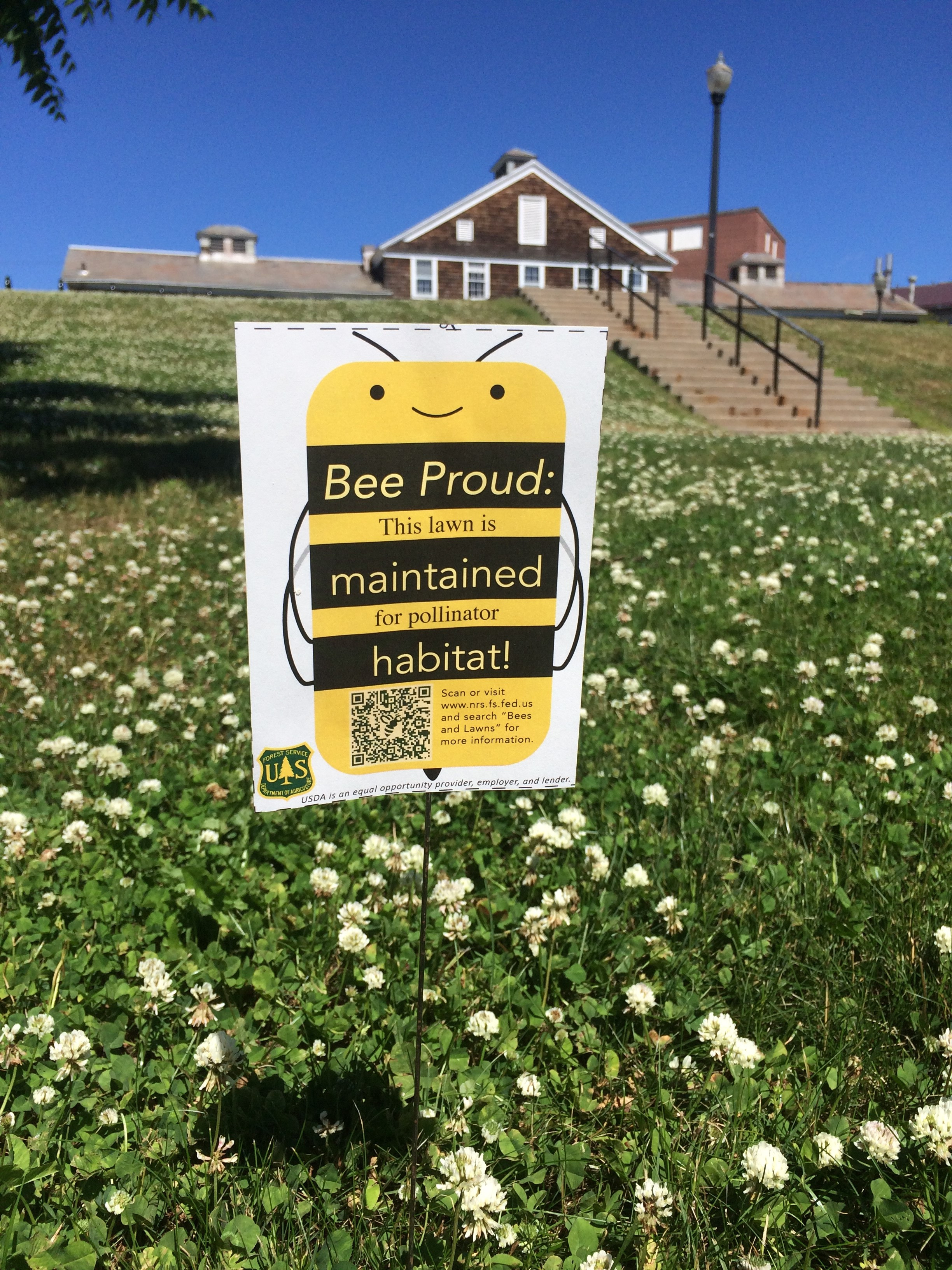 "A picture of a sign placed in the yard of a house that reads, ""Bee Proud: This lawn is maintained for pollinator habitat"""