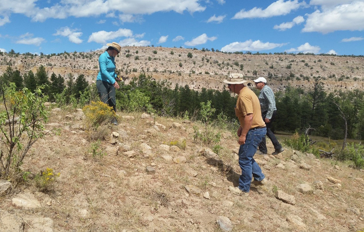 Photo: Three people on a hill inspect archaeological site.