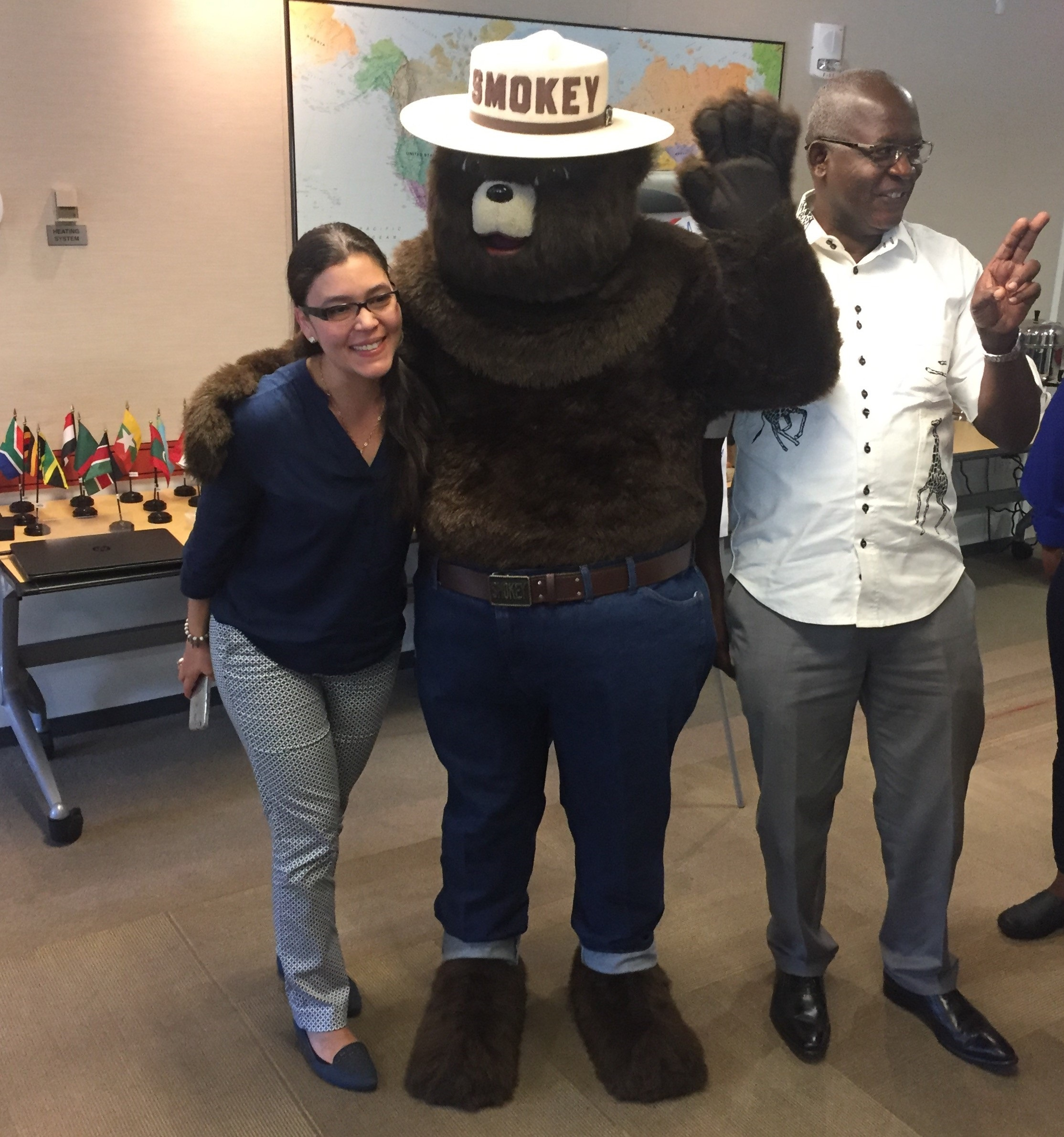 A woman from Colombia and a man from Congo pose next to Smokey Bear at the International Programs Office