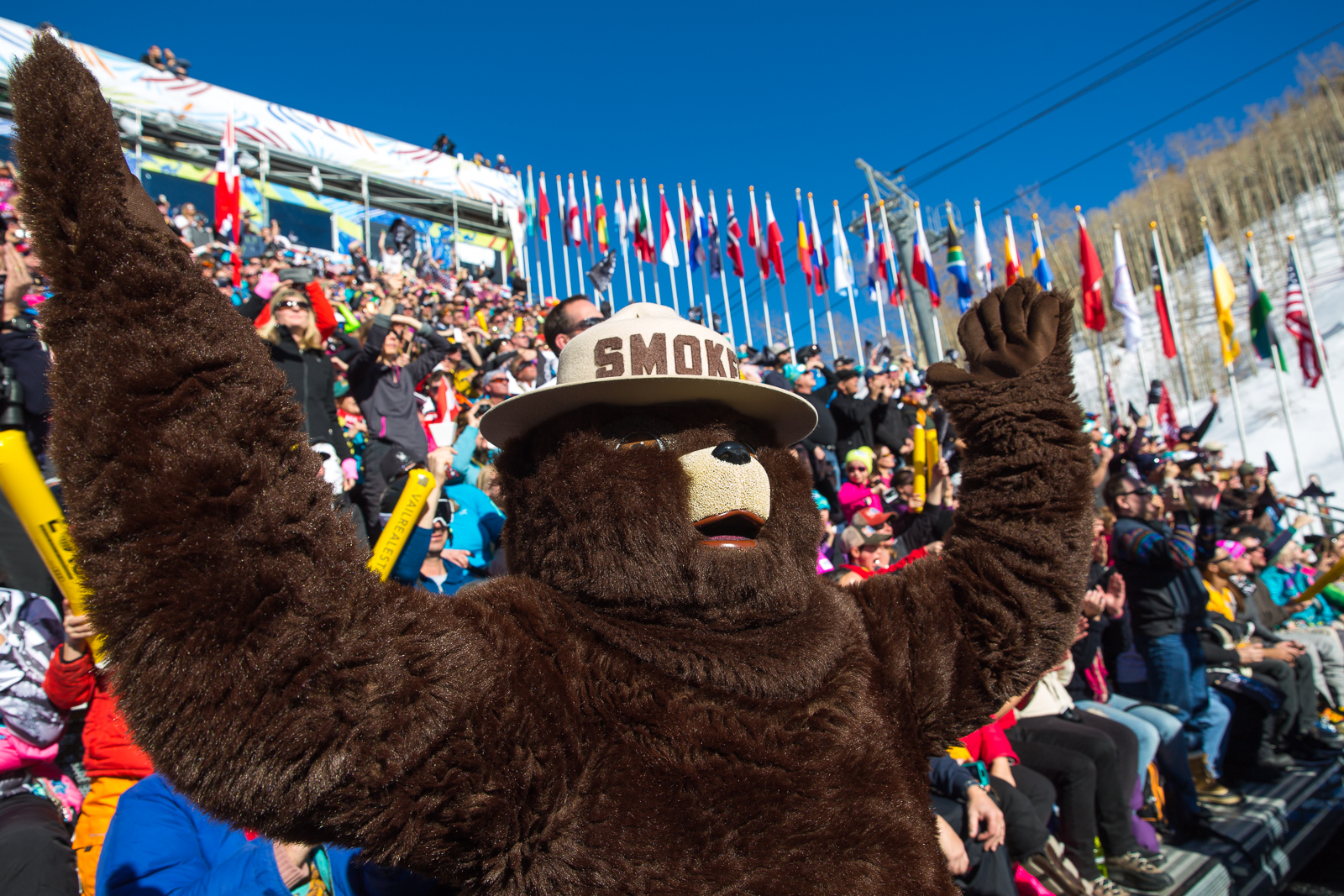 A picture of Smokey Bear in a crowd in the stands with his hands raised high in the air.