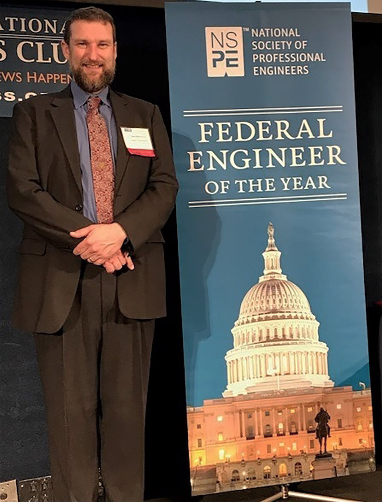 Photo: Man standing next to banner bug. Banner has image of U.S. Capitol at night below the text Federal Engineer of the Year.