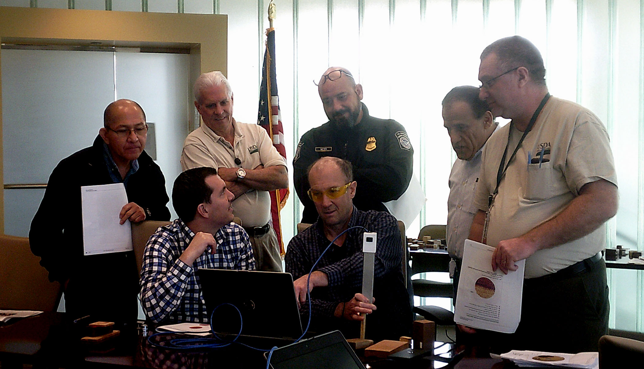Photo: Group of men gather around one who is demonstrating use of a tool to identify wood. They look over his shoulder as he points to something on a laptop screen.