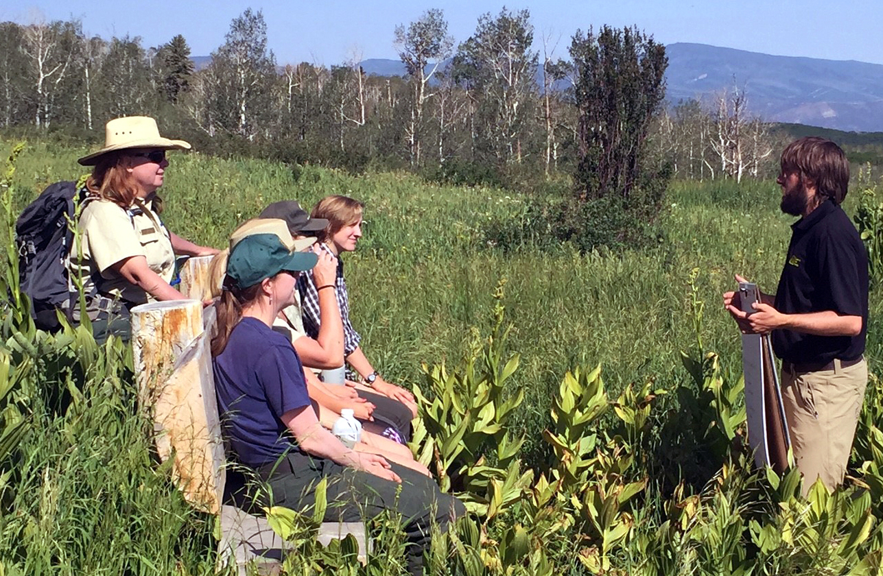 Photo: Man holding a flip chart talks to hikers standing in a meadow surrounded by aspen trees.
