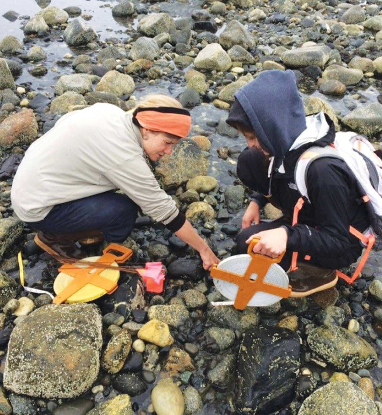 Two women scientists kneeling down near the water taking measurements and placling small marker flags.