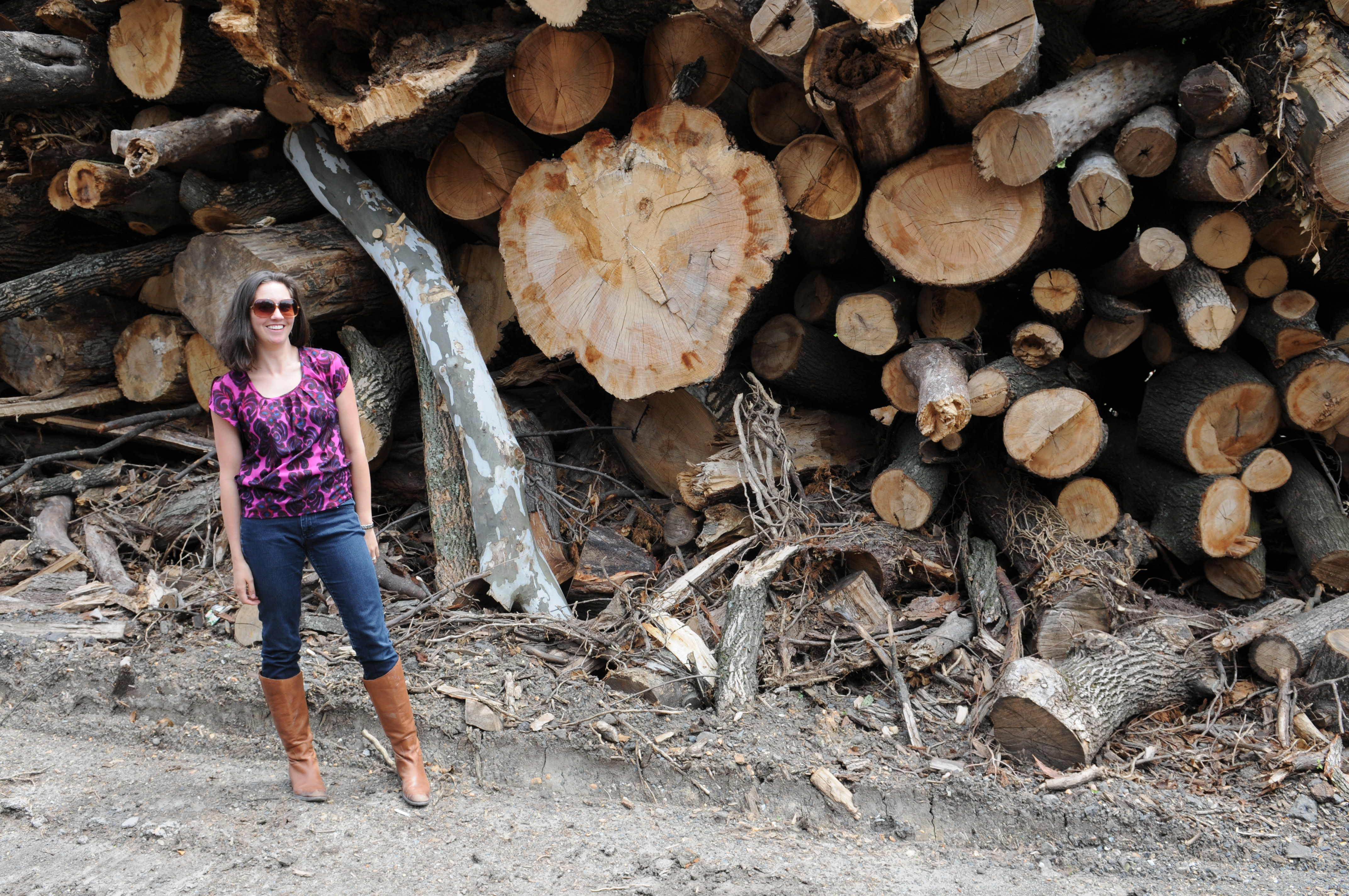 A picture of Lauren Marshall standing in front of a stack of cut trees.