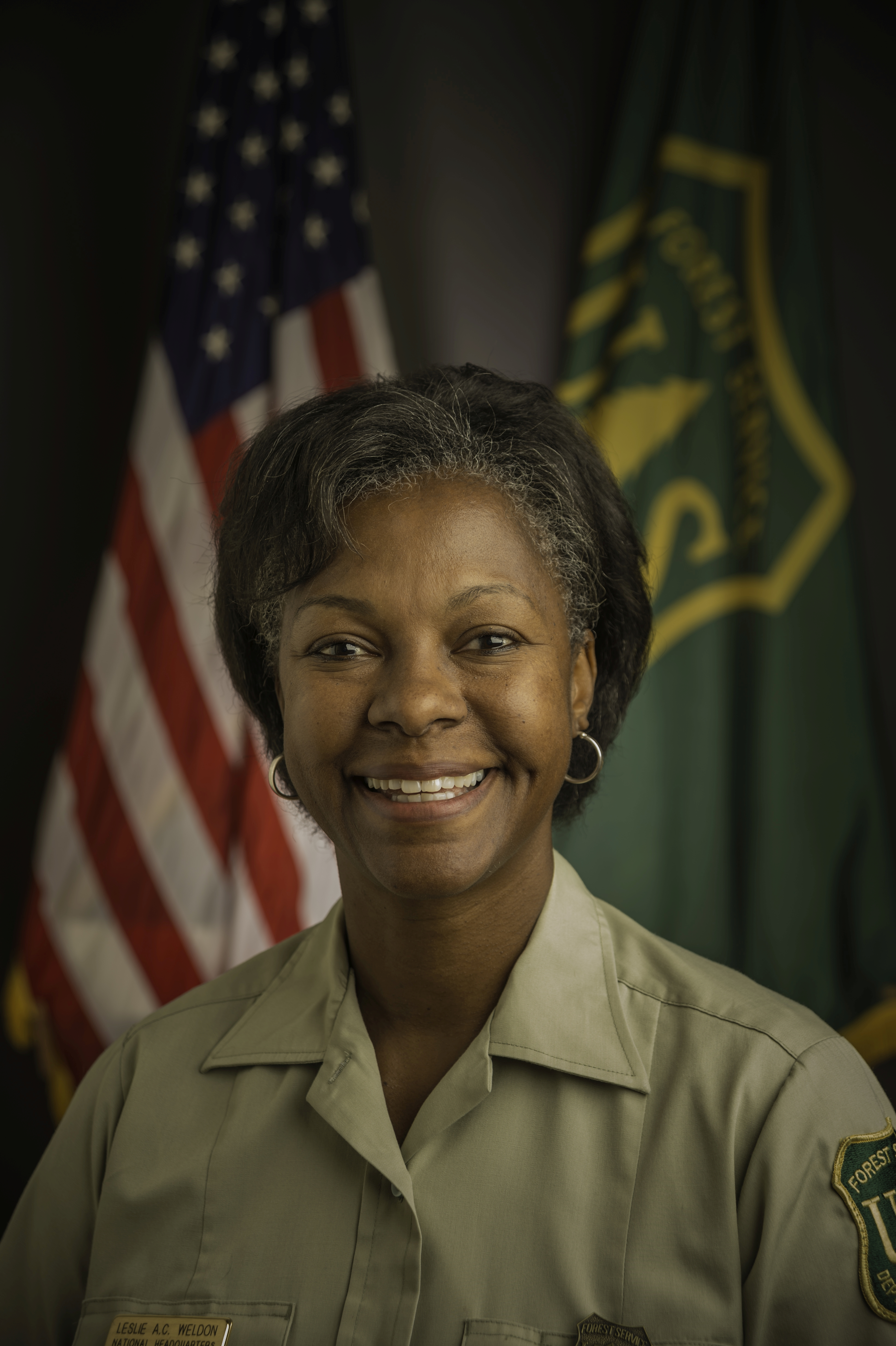 Photo: head shot of woman in Forest Service uniform. Behind her are the American and Forest Service flags.