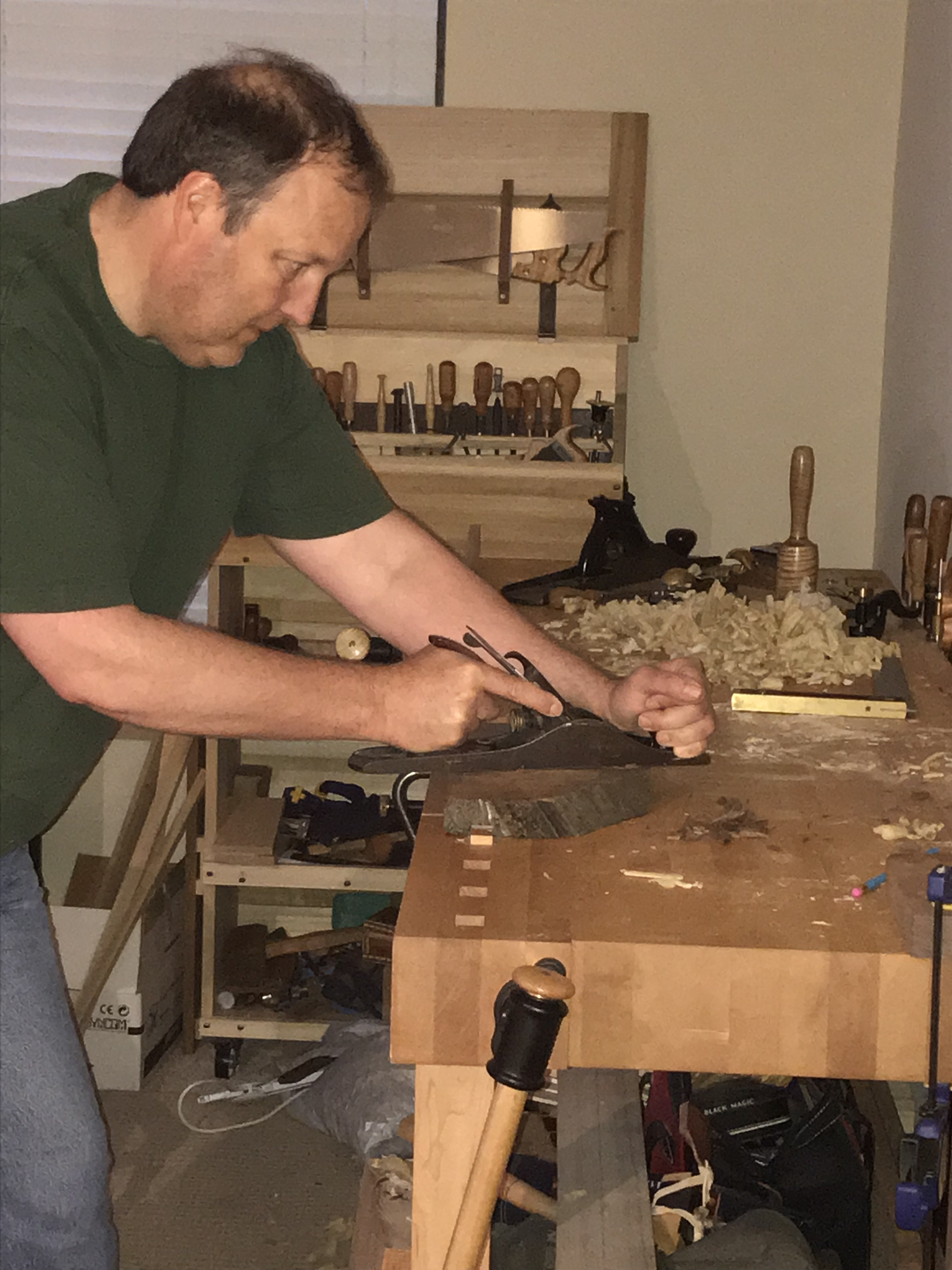 A picture of Scott Stewart at his workbench in his living room.