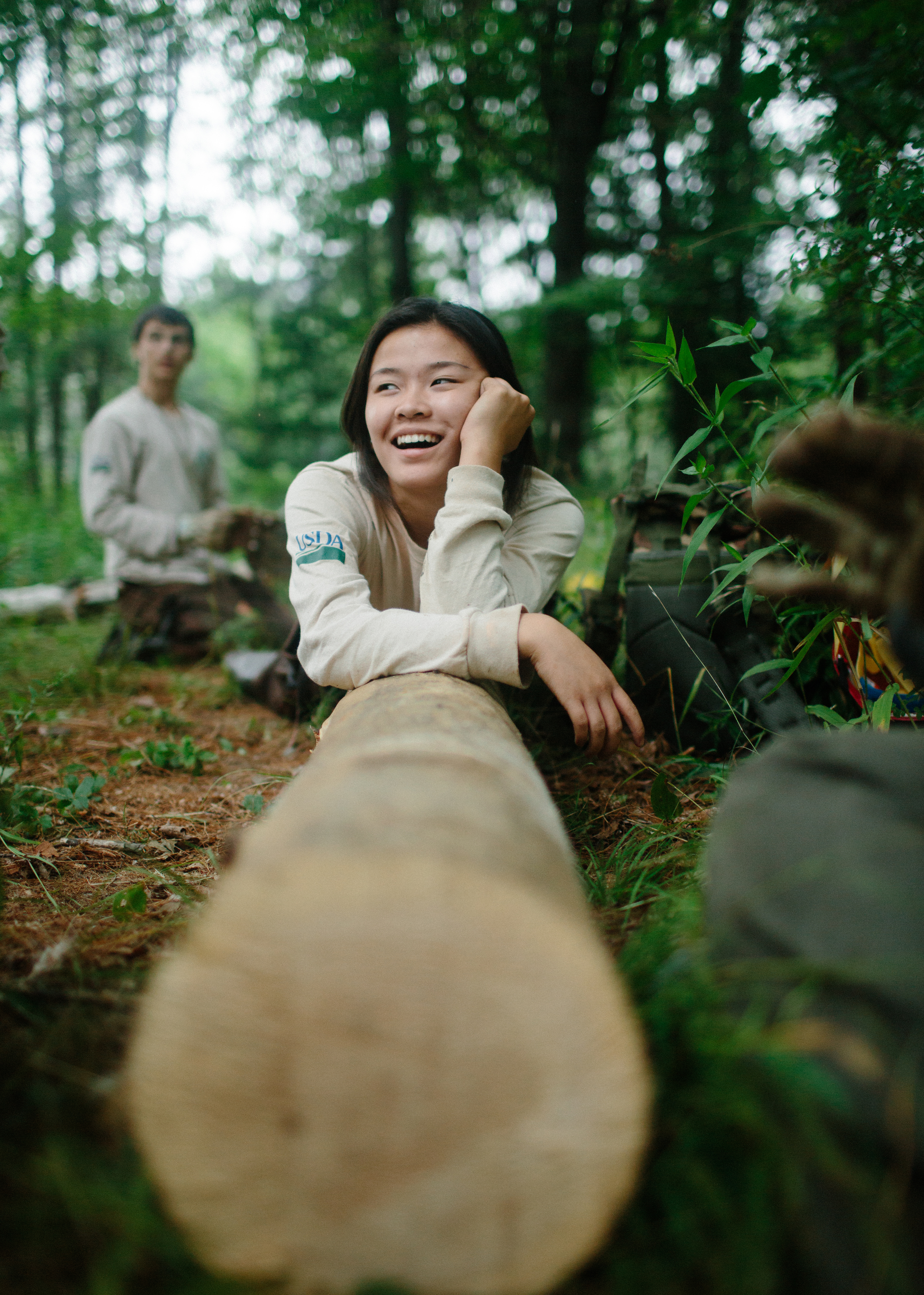 A photo of a Youth Conservation Corps crew members resting on a log