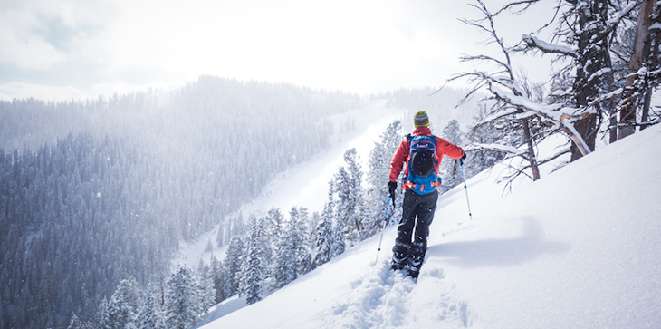 A picture of a person snowshoeing along the side of a snow-covered mountain.