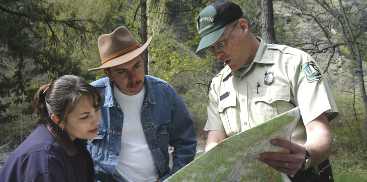 Forest Service employee showing a map to visitors.