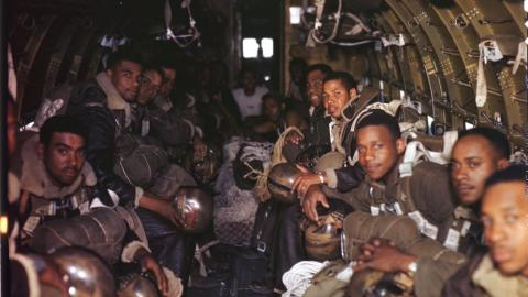 A picture showing several black parachutists sitting onboard an aircraft before a jump.