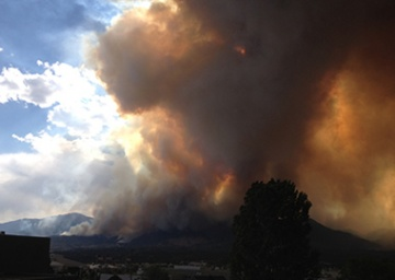 A large plume of smoke rises over Colorado Springs, Colo., that cast a wide,  dark shadow over homes and businesses.