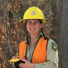 A picture of Lisa Barlow wearing a yellow Forest Service hard hat, orange vest and a Forest Service uniform.