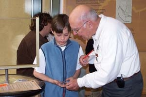 A photo of 2014 Enduring Service Awardee volunteer Jim Meade teaching a young boy how to string poles.