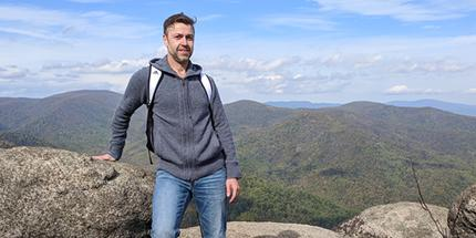 A picture of Aleksey hiking the Old Rag Mountain in Virginia; standing up on a high, rock area with a valley in the background.