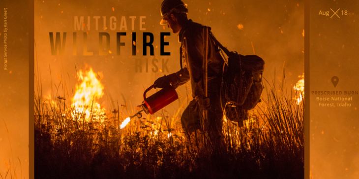 A close up shot of a firefighter holding a drip torch with fire all around him