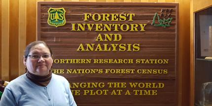 A picture of Peggy Castillo standing in front of a Forest Inventory and Analysis sign in the background.