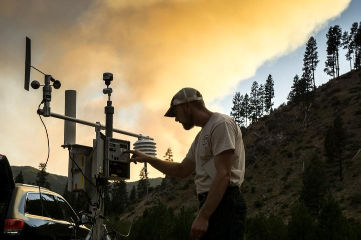 A picture of an air resource specialist using an air resource monitor near a wildfire.