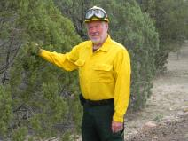 Daniel G. Neary is a supervisory research soil scientist in the Air, Water, and Aquatic Environments Program with the Rocky Mountain Research Station. Daniel is standing n the field, pointing at a copse of trees, in his Forest Service uniform.